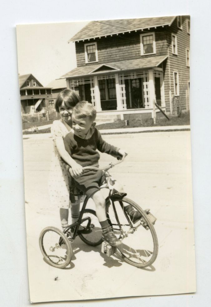 Little Bobby on a tricycle (note the decorative porch treatment in the background)