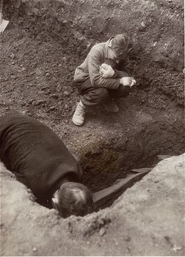 A Polish boy, Michael Kallaur, weeps while helping his father bury the body of his grandmother